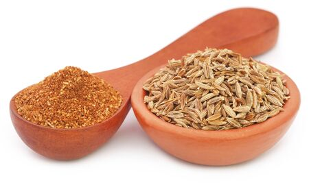 Crushed cumin with whole ones over white background