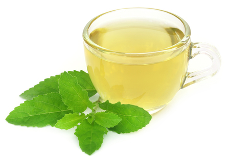tulsi: Herbal tea in a cup with tulsi leaves over white background