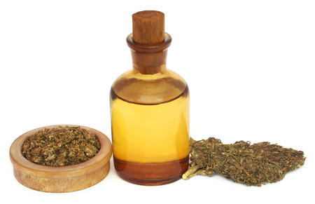 Medicinal cannabis with extract oil in a bottle over white background Stock Photo