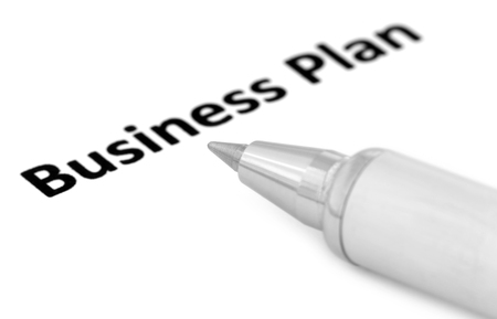 Business Plan written in a paper with a silver ballpoint