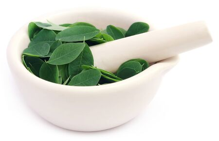 malunggay: Edible moringa leaves in a mortar with pestle over white background