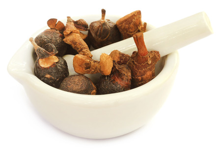 Soapnuts and sweet flag in a mortar with pestle over white background