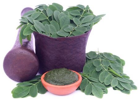 Edible moringa leaves in a vintage mortar with ground paste