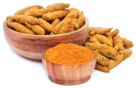 asian flavors: Whole and ground turmeric in bowl over white background