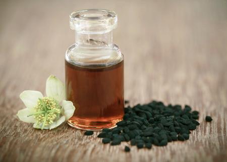 Kwiat Nigella z nasionami i olejkiem eterycznym w szklanej butelce