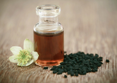 nigella seeds: Nigella flower with seeds and essential oil in a glass bottle Stock Photo