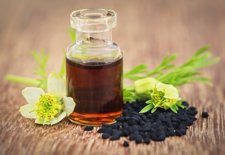 Nigella flower with seeds and essential oil in a glass bottle Stock Photo