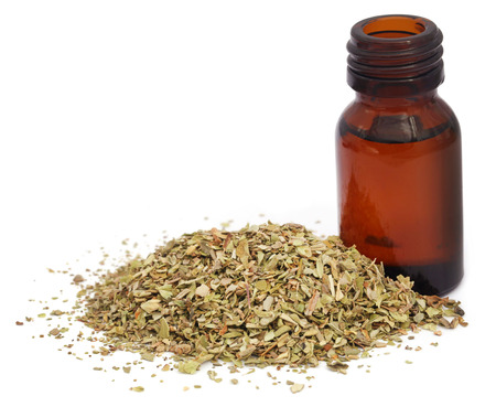 Dry oregano and essential oil in an amber bottle