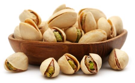 Closeup of some roasted pistachio in bowl over white background