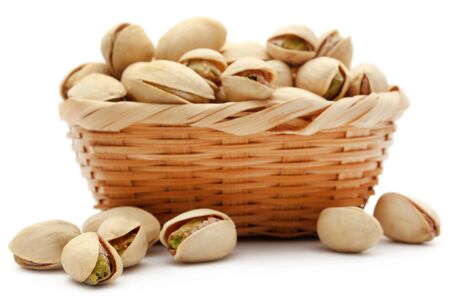 Closeup of fresh organic pistachio in basket over white background