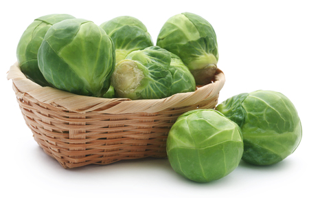 Rosenkohl or Brussels sprouts in a basket isolated over white background