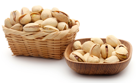 Closeup of some roasted pistachio in basket over white background Stock Photo