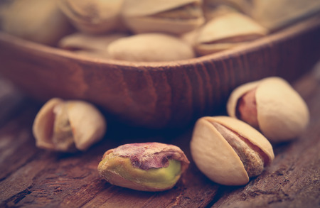 Closeup of some roasted pistachio in bowl on natural surface