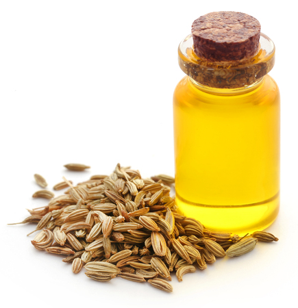 Fennel seeds with essential oil in a bottle over white background