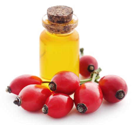 Medizinische Hagebutten mit ätherisches Öl in einer Glasflasche Standard-Bild - 98170592