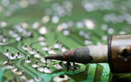 Television motherboard with soldering iron closeup Stock Photo