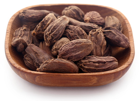 Black cardamom in bowl over white background