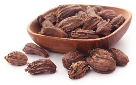 Black cardamom in a wooden bowl over white background