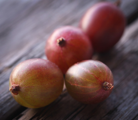 Fresh ripe gooseberry on wooden surface