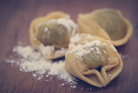 Italian Tortelloni made of spinach with flour on wooden surface Foto de archivo