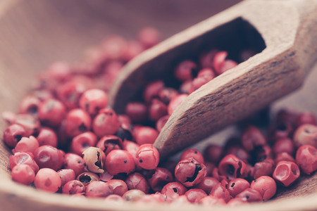 Pink peppercorn in a bowl with scooop Фото со стока