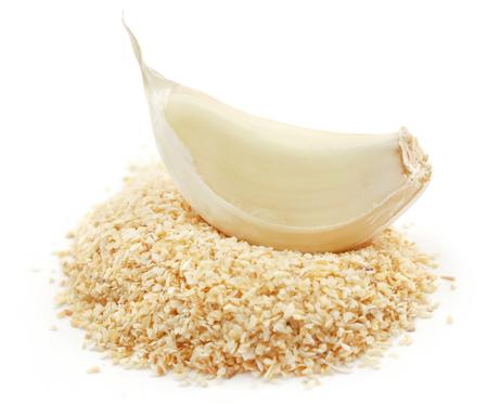 Garlic powder with piece of garlic over white background Фото со стока