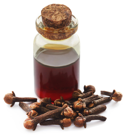 Fresh clove with oil in a jar over white background