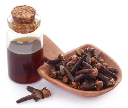 Clou de girofle frais dans une cuillère en bois avec de l'huile dans un bocal sur fond blanc