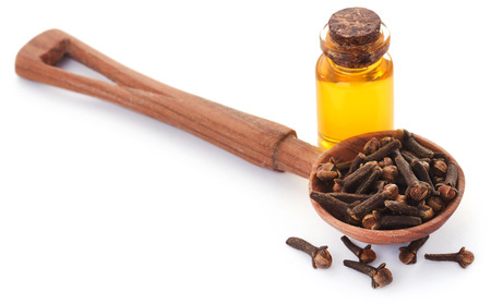 Fresh clove in a wooden spoon with oil in a jar over white background