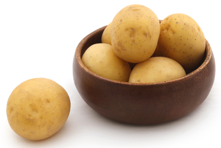 Fresh whole potatoes in a bowl over white background