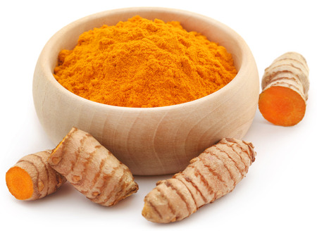 Raw turmeric with powder in a wooden bowl