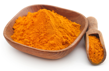 Powdered turmeric in wooden bowl with scoop over white background 免版税图像