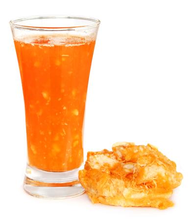 Fruta medicinal Bael con jugo en un vaso sobre fondo blanco.