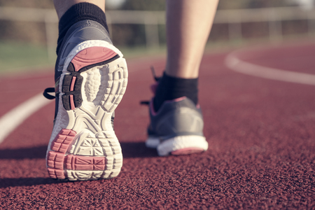 Woman running on athletic track at afternoon Stock Photo