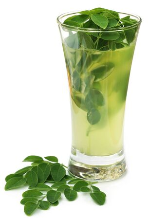 Moringa leaves with extract in a glass over white background Stock Photo
