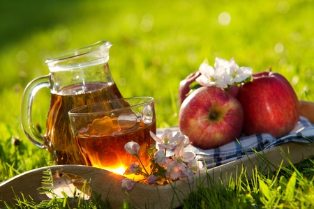 Apple juice and apples on wooden table on fresh green  backgroun