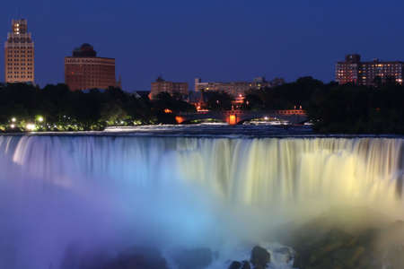 Waterfall with city at night above with lights photo