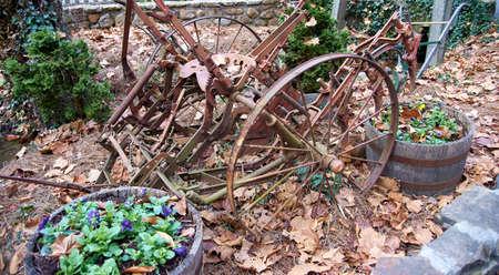 Rustic old farm machine sitting in fall leaves. 版權商用圖片