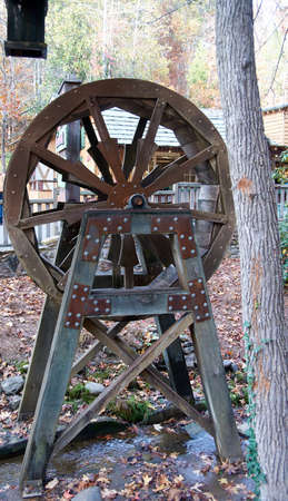 Rusitc wooden water wheel stand over small stream.