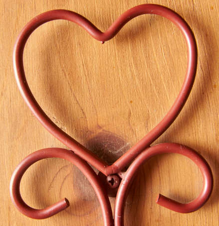 Heart shaped from brown metal wire with wood background.