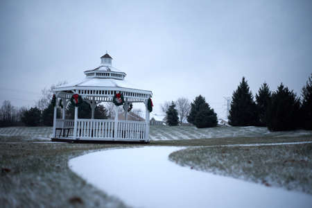 Outdoor gazebo with green christmas wreaths and red bow outside with snow cover.