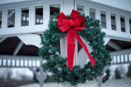 Green Christmas wreat with red bow hanging on outside gazebo.