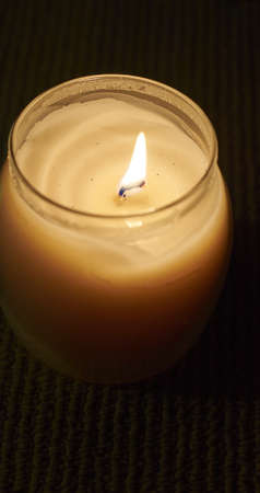 Small Candle with open flame burning in glass jar.