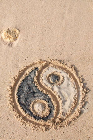 Yin-yang symbol drawn and filled with black and white sand at Melasti beach in Bali, Indonesia
