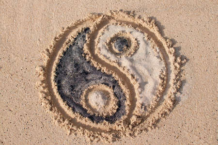 Yin-yang symbol drawn and filled with black and white sand at Melasti beach in Bali, Indonesia Stock Photo