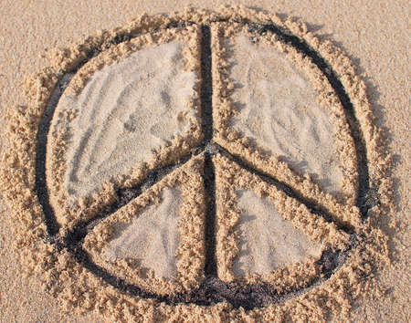 Peace symbol drawn and filled with black and white sand at Melasti beach in Bali, Indonesia