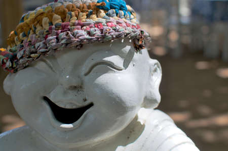Picture of a laughing porcelain statue that is wearing a colorful bonnet in Sanur (Bali), Indonesia Banque d'images