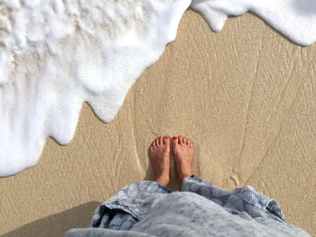 Top view on female legs and feet standing at the Melasti Beach in Bali, Indonesia while a wave is coming