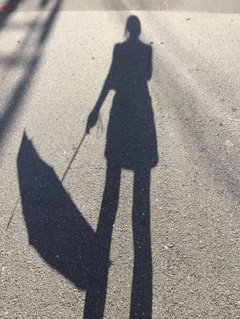 Picture of a shadow of a women holding down an umbrella on a sunny day in Kyoto, Japan