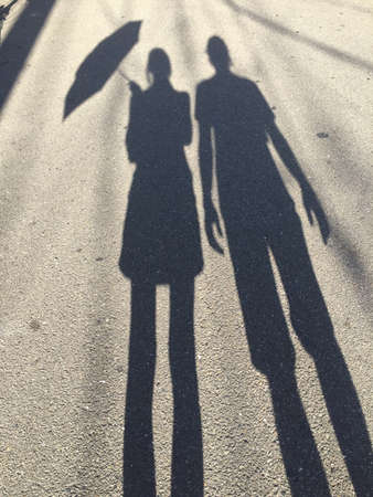 Silhouette picture of a women holding an umbrella and a man standing beside her